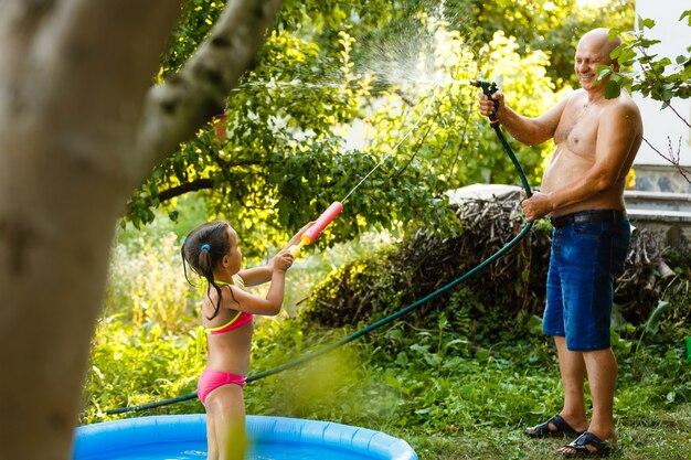 Abuelo con nieta jugando en una piscina inflable en un jardín.