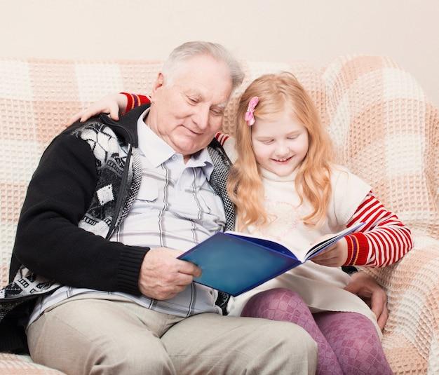 Abuelo y nieta sentados en el sofá y leyendo un libro