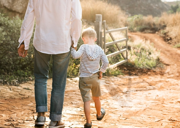 Abuelo y nieto caminando en la granja.