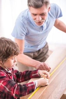 Abuelo y nieto con cinta métrica.