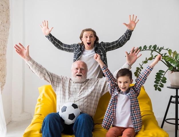 Abuelo con nieto e hijo regocijándose gol viendo el fútbol