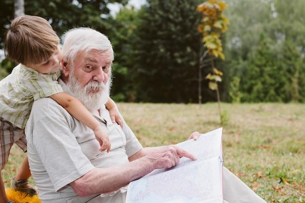 Abuelo y nieto en la hora del cuento del parque