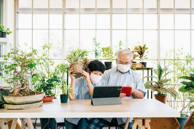 Abuelo y nieto de jubilación asiáticos con una mascarilla y viven para vender plantas en una tableta con diversión.