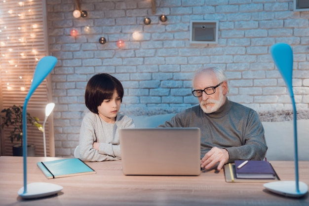 Abuelo y nieto usando la computadora portátil juntos