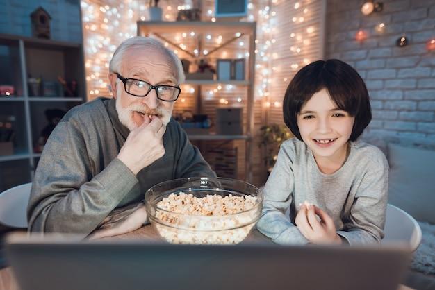 Abuelo y nieto viendo películas en la computadora portátil