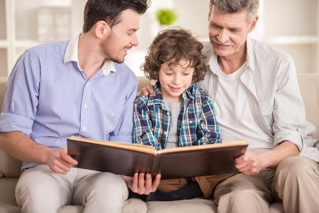Abuelo, padre e hijo sentado y leyendo libro en sofá
