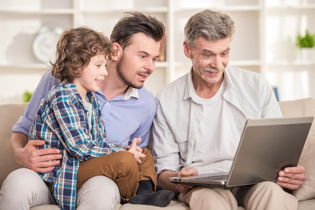 Abuelo padre e hijo sentados y usando la computadora portátil en el sofá.