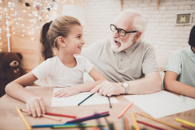El abuelo de pelo gris enseña a la niña feliz a dibujar.