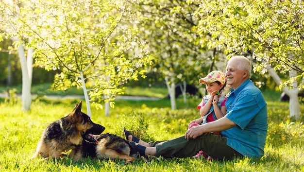 Abuelo con perro nieta y un perro en el jardín