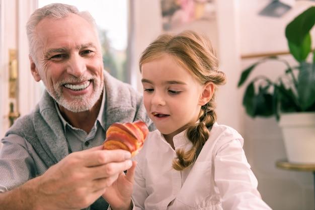 Abuelo radiante. radiante abuelo barbudo sonriendo mirando a su niña probando croissant en la cafetería