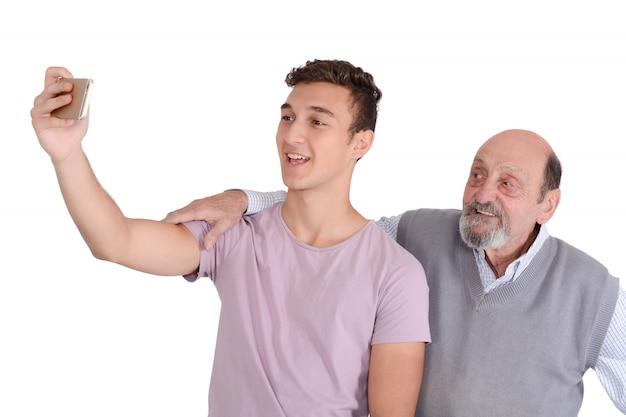 Abuelo y su nieto adolescente tomando un selfie.