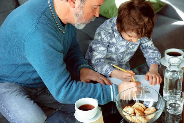 El abuelo y su nieto pasan tiempo aislados en casa, estudiando