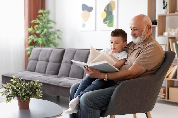 Abuelo de tiro medio leyendo a niño