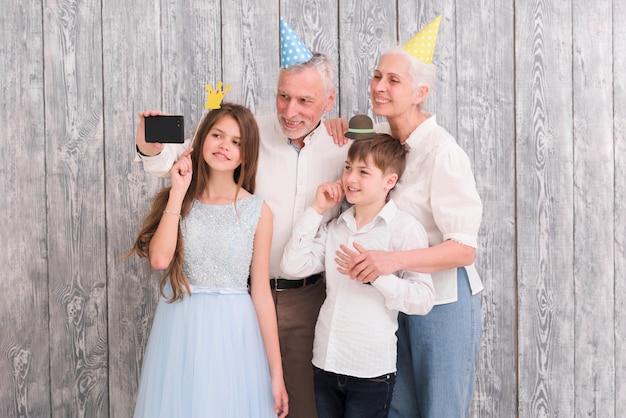 Abuelo tomando selfie en su teléfono móvil con su esposa y nietos usando accesorios