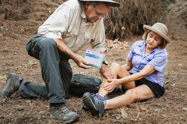 Abuelo usando botiquín de primeros auxilios para cuidar a la abuela