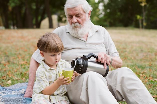Abuelo vertiendo té para nieto
