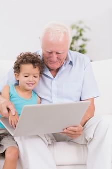 Abuelo y nieto mirando una computadora portátil