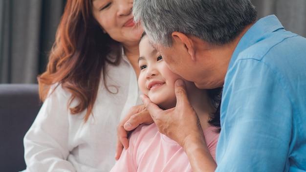 Los abuelos asiáticos besan la mejilla de la nieta en casa. los chinos mayores, la vieja generación, el abuelo y la abuela que usan el tiempo familiar se relajan con el niño de la chica joven que miente en el sofá en concepto de la sala de estar.