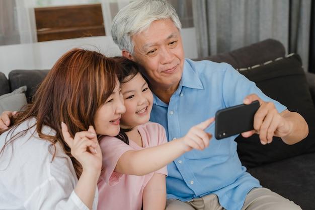 Abuelos asiáticos selfie con nieta en casa. los chinos mayores, el abuelo y la abuela felices pasan el tiempo en familia relajándose usando el teléfono móvil con el niño de la niña acostado en el sofá en concepto de sala de estar.