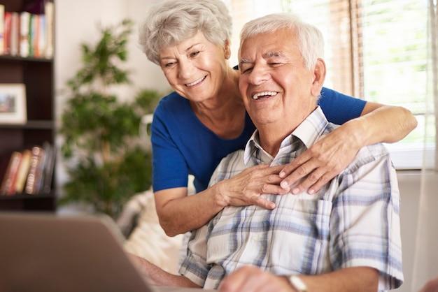 Abuelos felices usando su computadora portátil digital