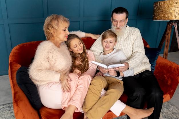 Abuelos leyendo un libro con sus nietos.