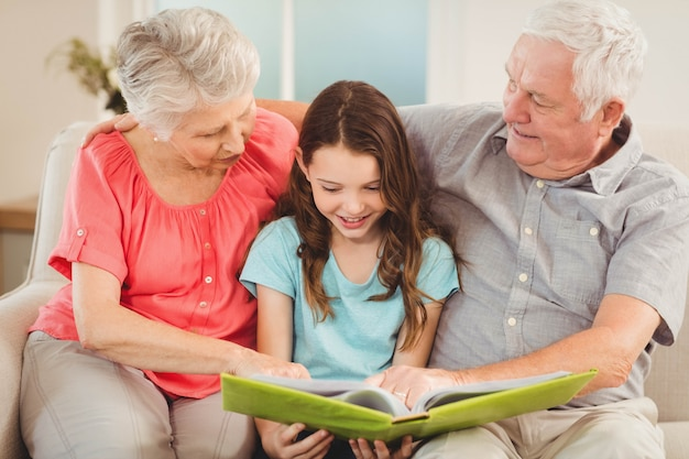 Abuelos y nieta sentados en el sofá y leyendo un libro con nieta