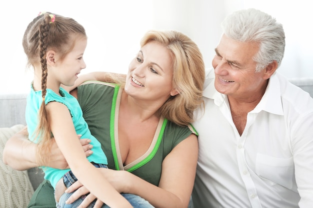 Abuelos con nieta en el sofá