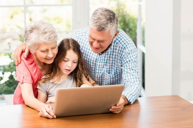 Abuelos y nieta usando laptop en casa