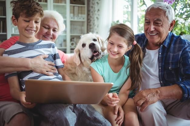 Abuelos y nietos que usan una computadora portátil en la sala de estar