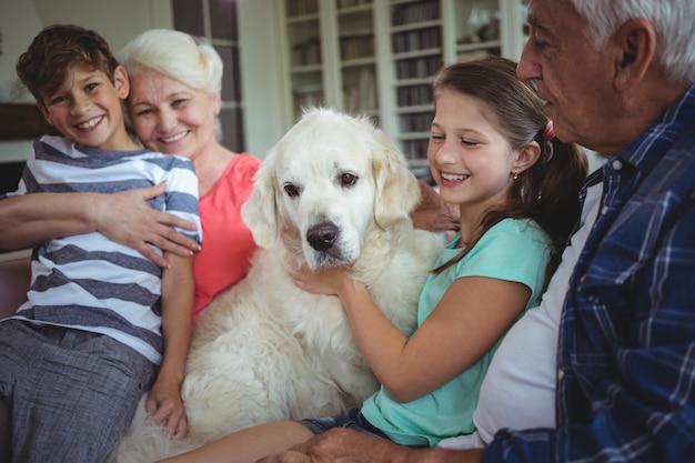 Abuelos y nietos sentados en el sofá con una mascota