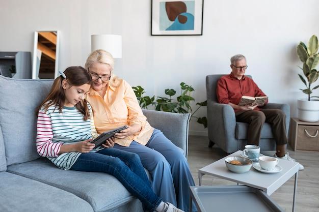 Abuelos y niña con laptop en interiores