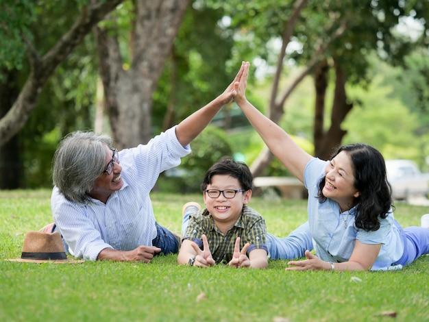 Los abuelos pasan el tiempo con su nieto, están sentados en la hierba en el jardín en casa.