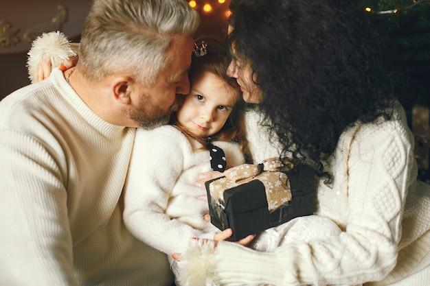 Abuelos sentados con su nieta. celebrando la navidad en una casa acogedora.