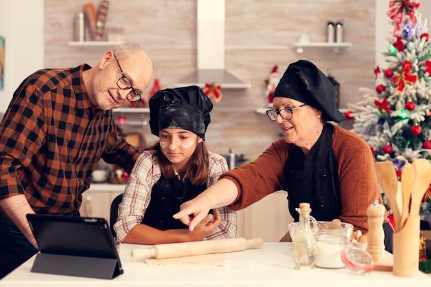 Abuelos y sobrina buscando receta en navidad