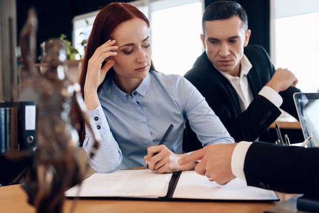 Abult pareja pasando por divorcio firmando documentos.