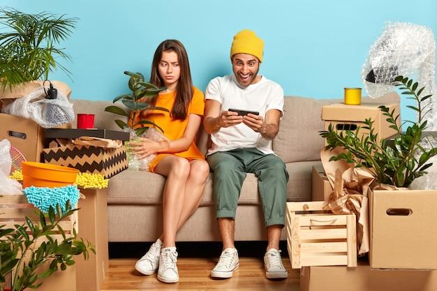Aburrida mujer europea sostiene una maceta con una planta de interior verde, mira a un lado la pantalla del teléfono inteligente, observa cómo su novio juega juegos en línea, se mudan juntos en un apartamento recientemente comprado