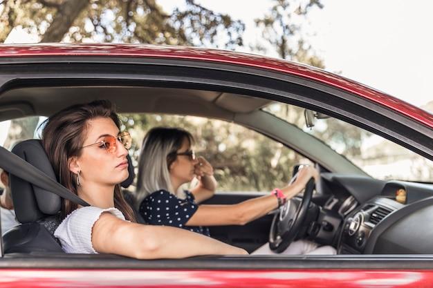 Aburrida mujer joven que viaja en coche moderno con su amigo