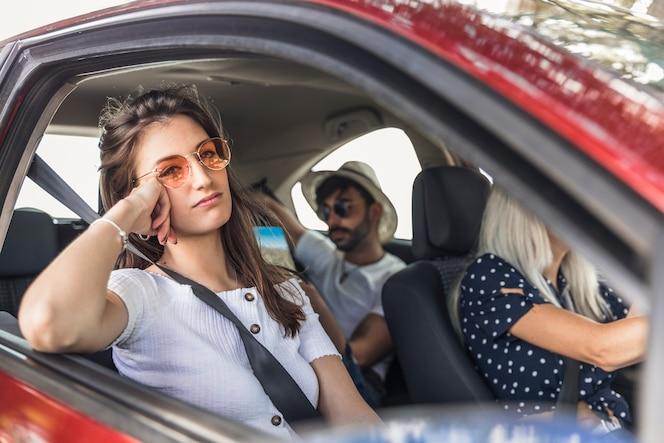 Aburrida mujer joven que viaja en coche moderno con sus amigos