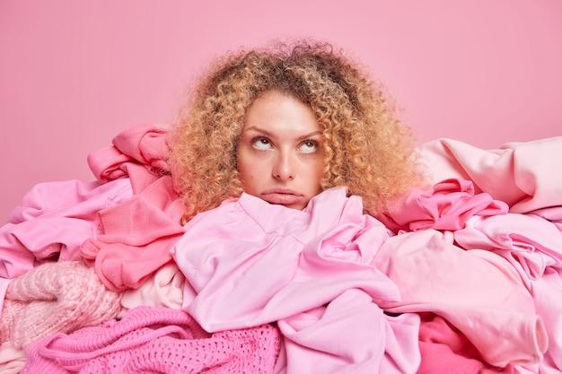 Aburrida mujer joven triste con cabello rizado y tupido posa alrededor de montones de ropa enfocada arriba aislada sobre pared rosa. armario femenino desordenado. reciclaje de tejidos y concepto de reutilización textil.