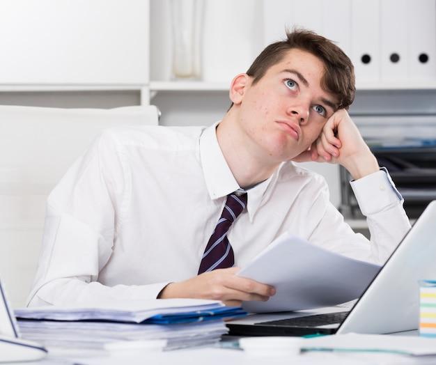 Aburrido adolescente leyendo documentos cerca de la computadora portátil