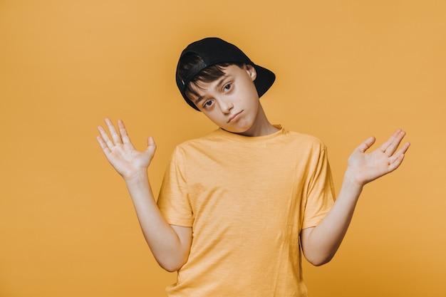 Aburrido, apuesto joven vestido con una camiseta amarilla y una gorra de béisbol, extiende sus manos, dudando.
