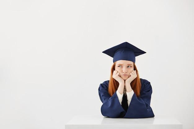 Aburrido cansado mujer graduada pensando sentado sobre fondo blanco copiar el espacio.