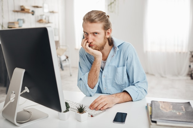 Aburrido empleado de oficina caucásico barbudo con una mirada desesperada que se acerca a la fecha límite, pero no puede terminar el informe a tiempo. hombre empleado sentado frente a la computadora en la luz, escribiendo informe.