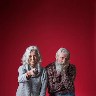Aburrido senior hombre viendo la televisión con su esposa contra el telón de fondo rojo