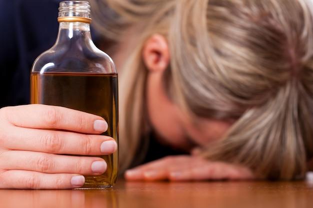 Abuso de alcohol - mujer bebiendo demasiado brandy