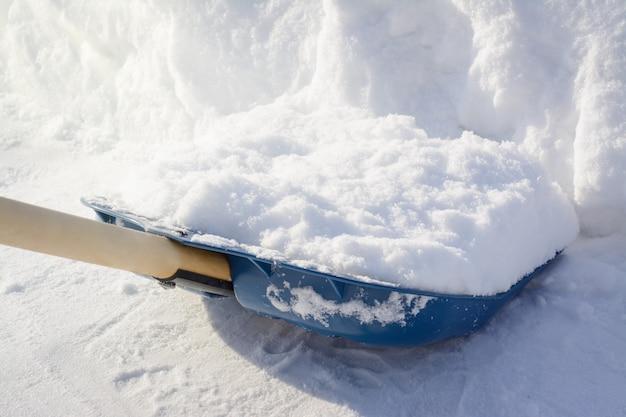 Acabado de palear nieve en el pavimento. pala de nieve cerca de un gran banco de nieve mientras limpia