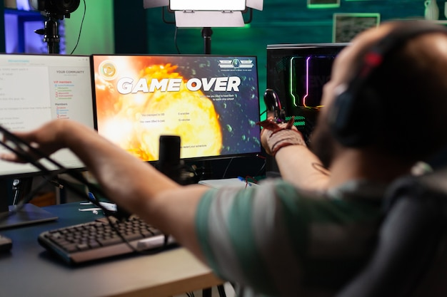 Se acabó el juego para serpentinas de hombres que juegan al juego de disparos espaciales en línea con un moderno asiento para la cabeza y un joystick. cyber actuando en una poderosa pc hablando con los jugadores en el chat abierto durante la competencia profesional