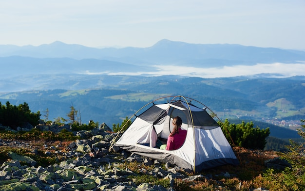 Acampar en la cima de la montaña en la brillante mañana de verano