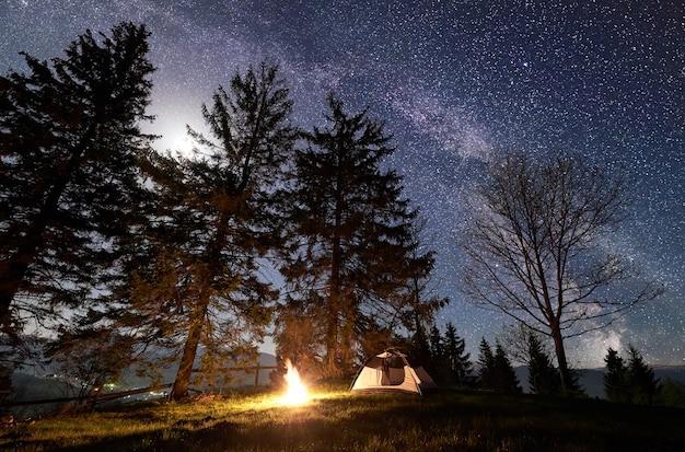 Acampar de noche en las montañas bajo el cielo estrellado y la vía láctea.