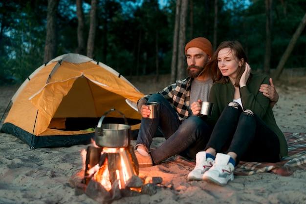 Acampar pareja bebiendo juntos por fogata